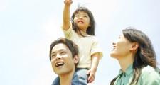 娘を肩車する父親とそばに立つ母親