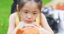 Outdoor upset Asian child. Little girl showing her unhappy face.